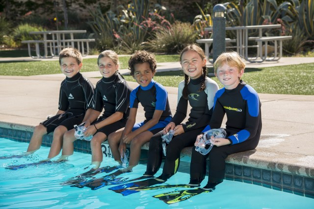 A group of kids sitting on the edge of a pool waiting for a scuba diving lesson