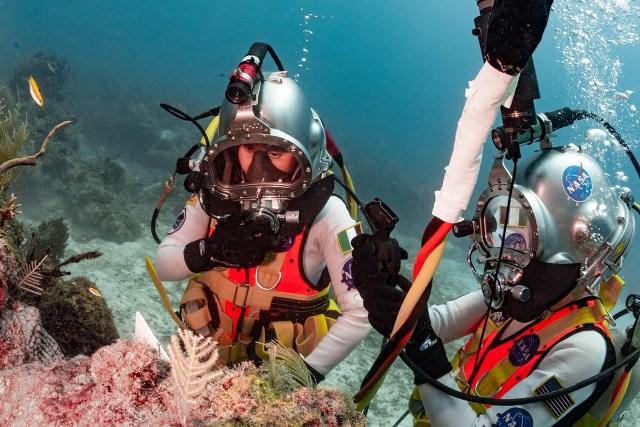 Two NASA astronauts wearing dive helmets working underwater