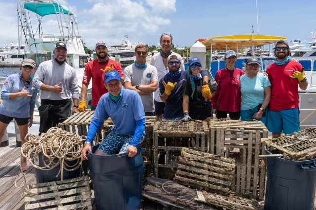 Fabien Cousteau sits with debris removed from a Florida Keys reef.