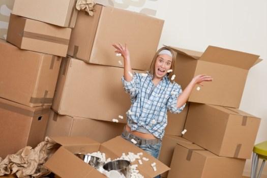 Cutii din carton refolosite la mutare relocare. Femeie ambaleaza produse in cutii de carton.