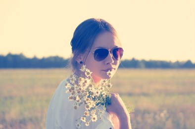 portrait-of-young-woman-wearing-sunglasses-and-holding-wildflowers-in-meadow