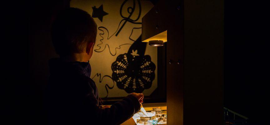Enfant dessinant avec les objets et la lumière