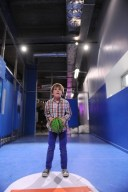 Enfant se concentrant pour marquer un panier au basket dans l'exposition Sport