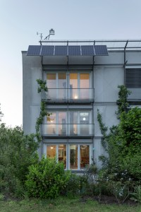 The first Passive House building from the garden, showing the solar photovoltaic system