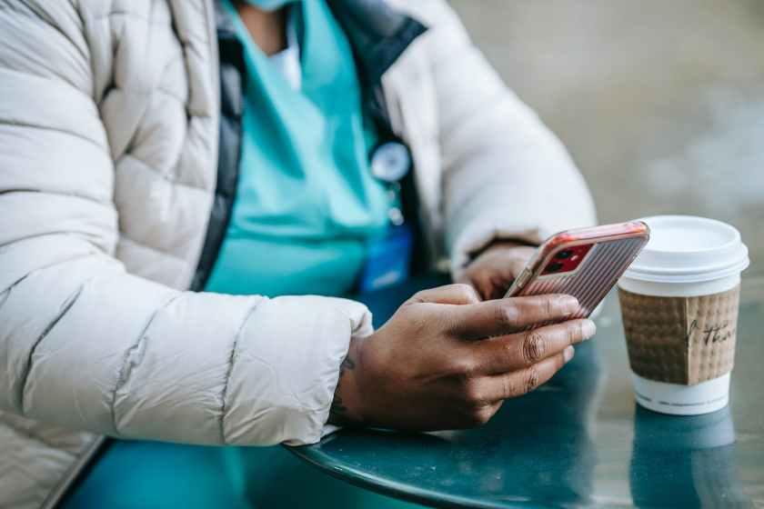 crop unrecognizable black nurse using smartphone in outdoor cafe