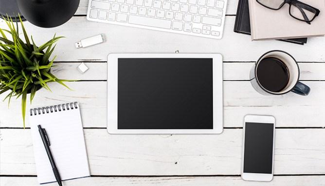 laptop, tablet en smartphone liggen op een bureau