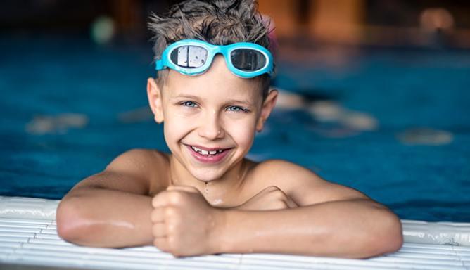 Jongetje hangt aan de rand van het zwembad en draagt een zwembril op sterkte