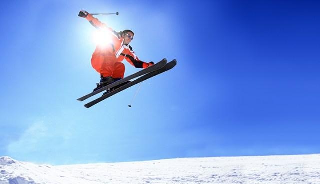 skiër springt van heuveltje met sportzonnebril