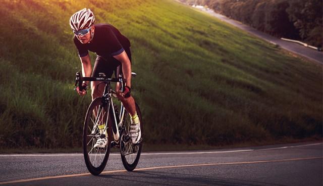 wielrenner fietst met wrap around zonnebril de berg op