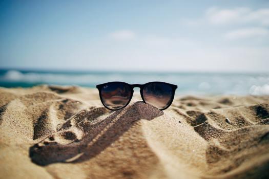 Ray-Ban zonnebril op strand met zee op de achtergrond