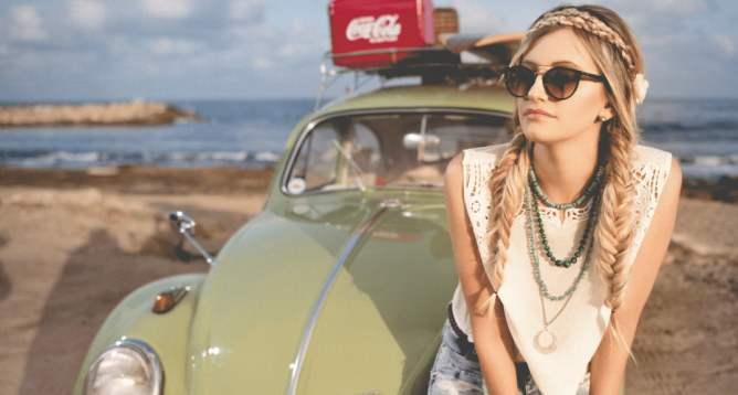 Vrouw met Ray-Ban zonnebril leunt op een Volkswagen Kever