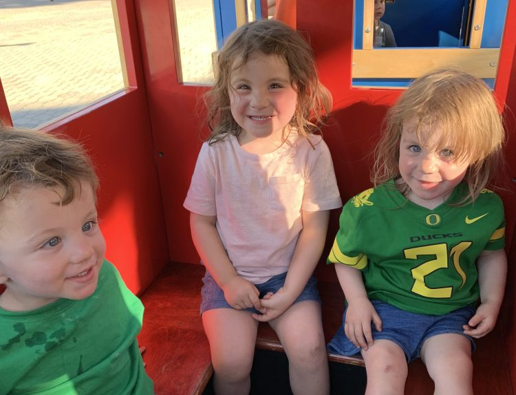 Three young children sitting inside of a toy train ride.