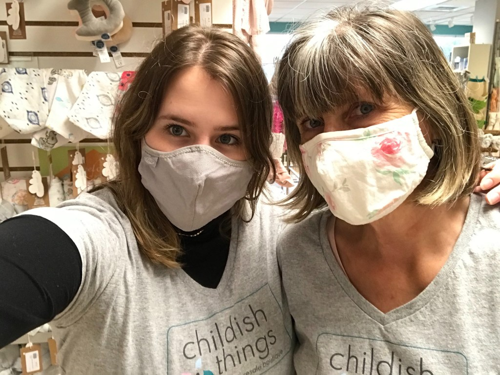 A mother is standing to the left of her teenage daughter. The mother is wearing a cream-colored mask with a pink roses pattern. The daughter is wearing a solid light grey mask and has her left arm draped on her mother's shoulder, while her right arm is extended, holding out the camera to take this photo. Both women are wearing light grey, short-sleeved V-neck t-shirts with the Childish Things logo seen on the chest, leaning their heads in towards one another.