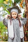 Preschool-aged girl standing in a silver-grey graduation gown and cap.