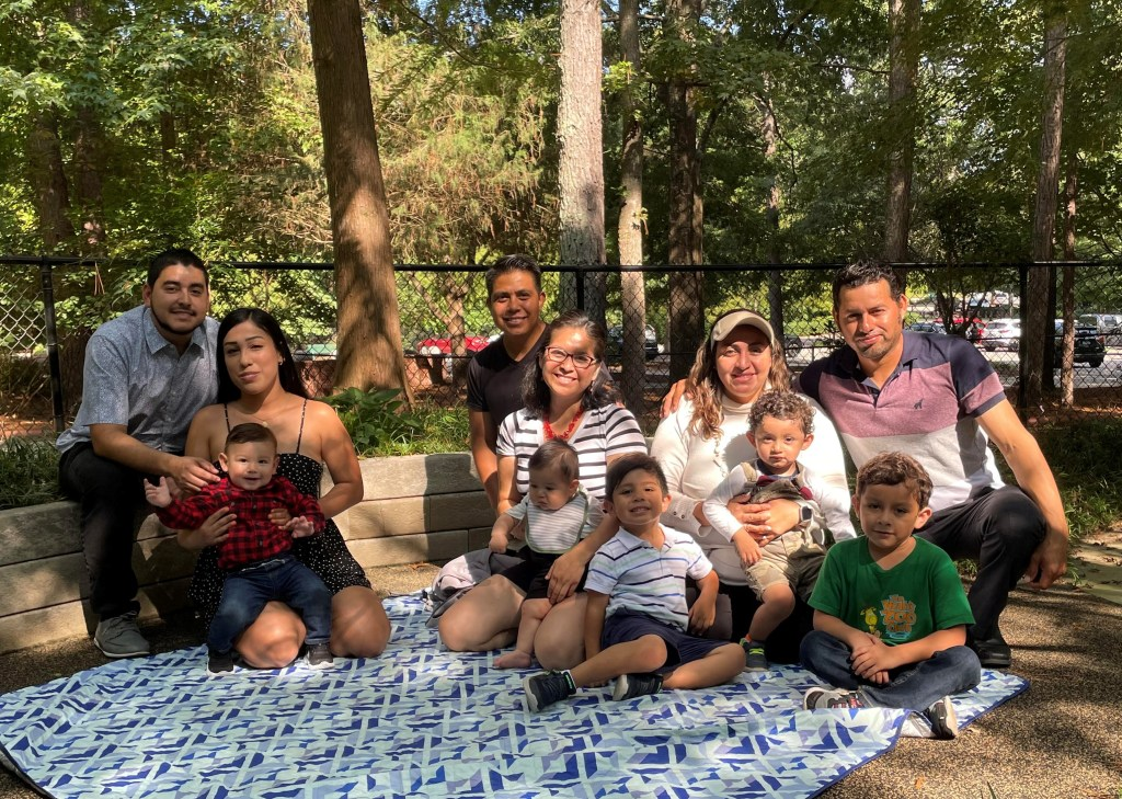 Three sets of parents sit outside with their young children on a picnic blanket.