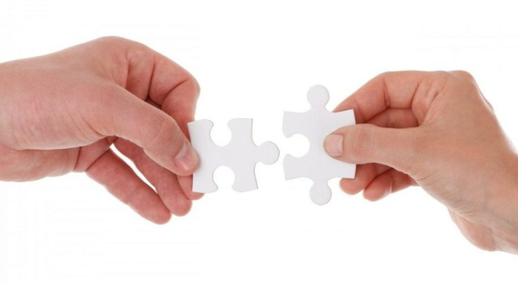 two hands connecting white puzzle pieces together