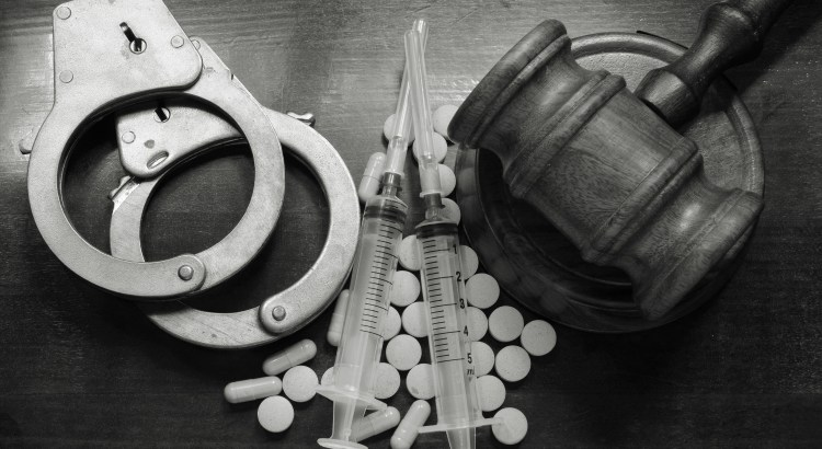greyscale handcuffs, pills and gavel