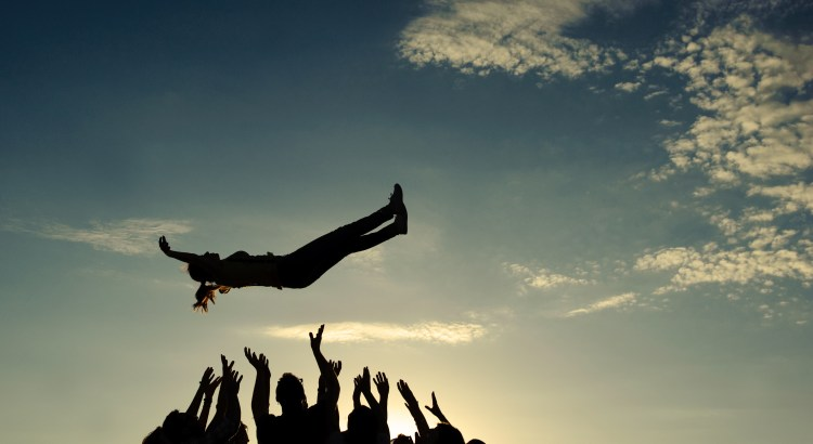 Silhouette of a group of people throwing up someone in the air