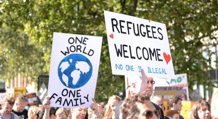 """protesters carry signs that say """"refugees welcome"""" in"""