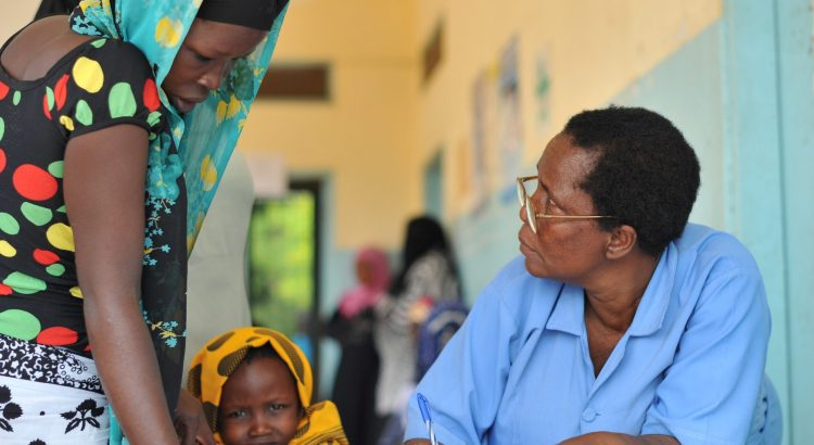 A doctor in Mtimbwani, Tanzania helps a woman and child.