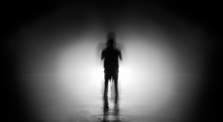 blurry, shadowy human figure in black and white
