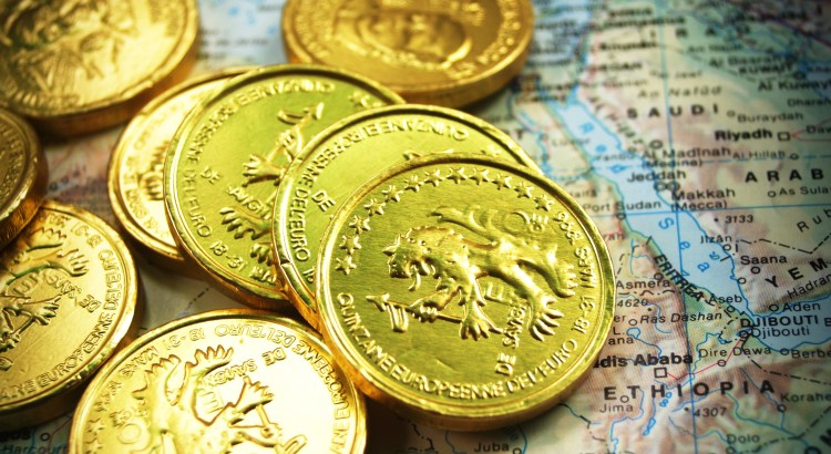 Image of a pile of gold coins on top of a map showing African continent