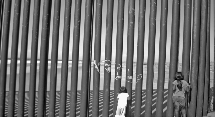 Black and white image of children playing in the fence at the US-Mexico border.