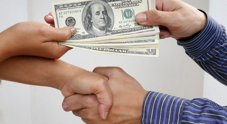 Image of two people shaking hands and exchanging money.
