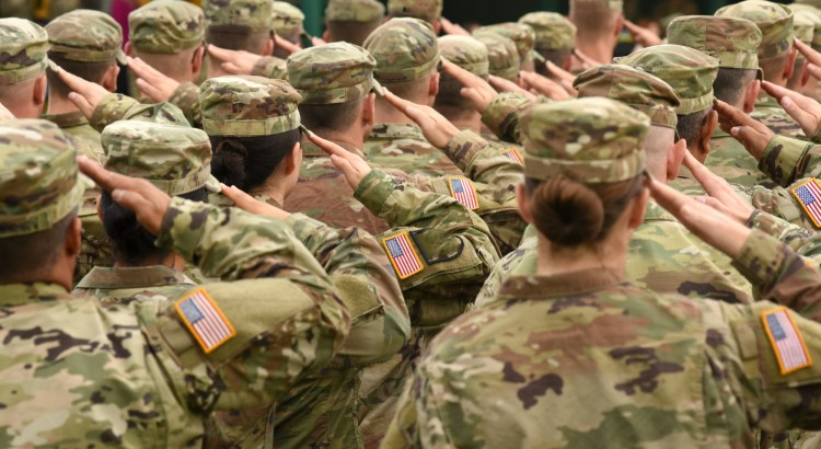 US servicemembers pictured from behind, saluting