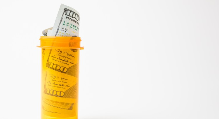 Hundred dollar bills rolled up in a pill bottle