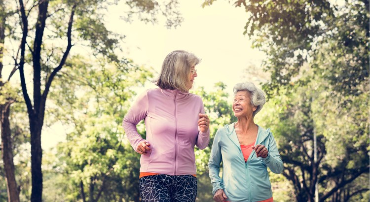 Two senior women jogging in a park