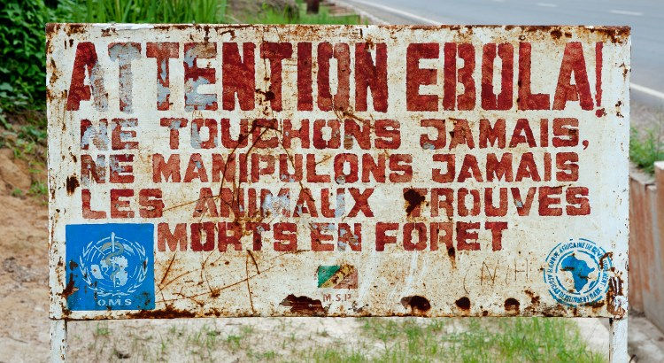 "Worn-down sign with a WHO sign that reads ""Attention Ebola!"""