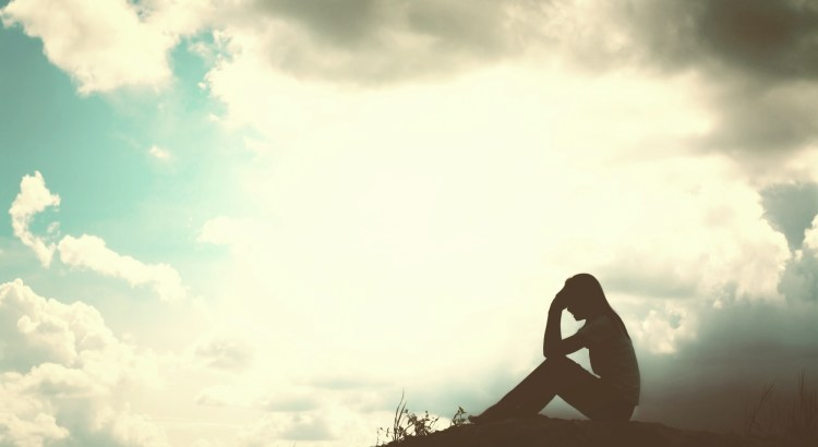 Silhouette of a woman sitting with her hand to her forehead on a hill