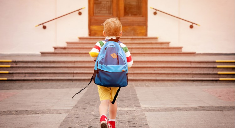 Back view of a little boy wearing a backpack walking to school