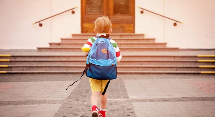 Back view of a little boy wearing a backpack walking to school