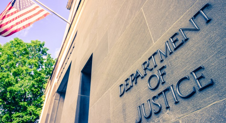 Image of the Department of Justice building with a U.S. flag hanging from it