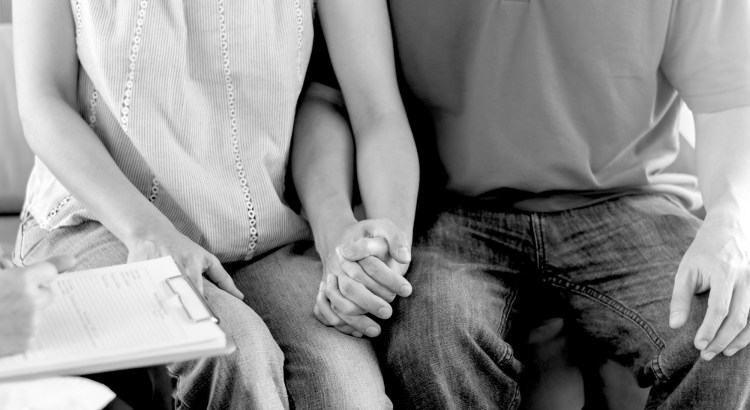Man and woman on holding hands on a couch, pictured from the neck down