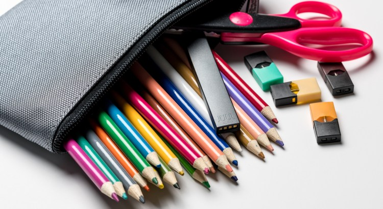 Photo of pencil case filled with colored pencils and an e-cigarette
