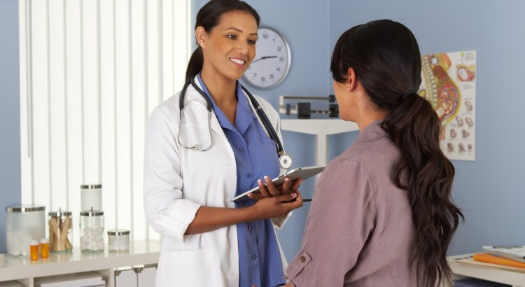 Female gynecologist talking to female patient while holding a tablet