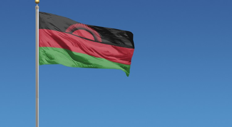 Flag of Malawi blowing in the wind in front of a clear blue sky