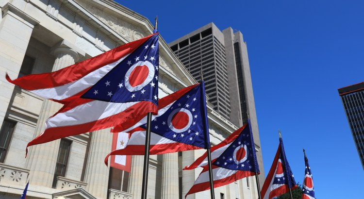 Ohio state flags waving in front of the Ohio State House