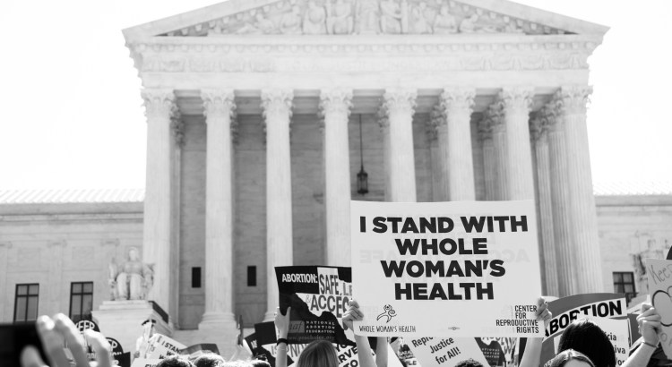 "Black and white photograph of the front of the Supreme Court. Pro-abortion protestors stand holding signs, one of which reads ""I stand with Whole Woman's Health"""