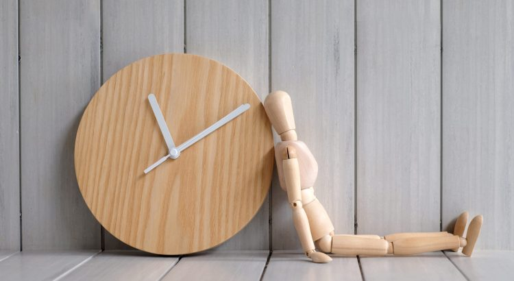Wooden figurine of a person leans against a wood wall clock