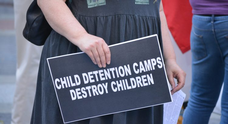 """People taking part in the """"Lights4Liberty"""" protests against President Trump's planned ICE raids against immigrants and the detention centers along the southern border. The protestor is carrying a sign that reads, """"Child detention camps destroy children."""""""