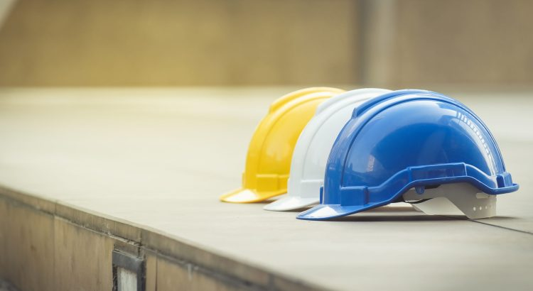 Three hard hats for construction work lined up on a concrete wall