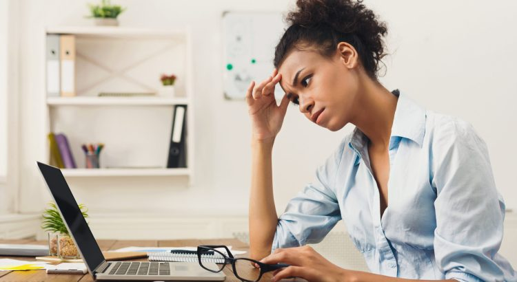 A frustrated woman sits at her desk, staring at her computer. Her head is resting in her hand