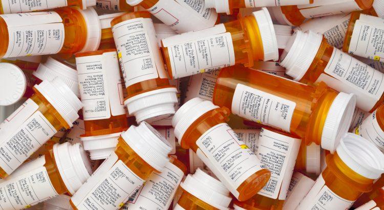 Large pile of amber prescription pill bottles