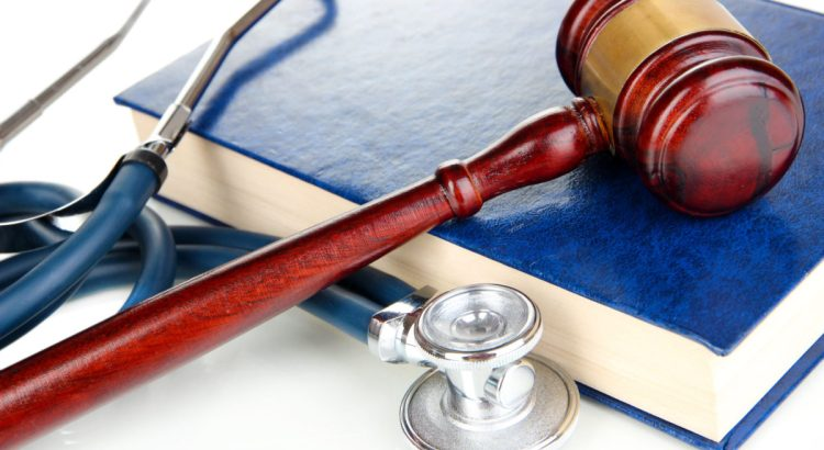 Medicine law concept. Gavel and stethoscope on book close up
