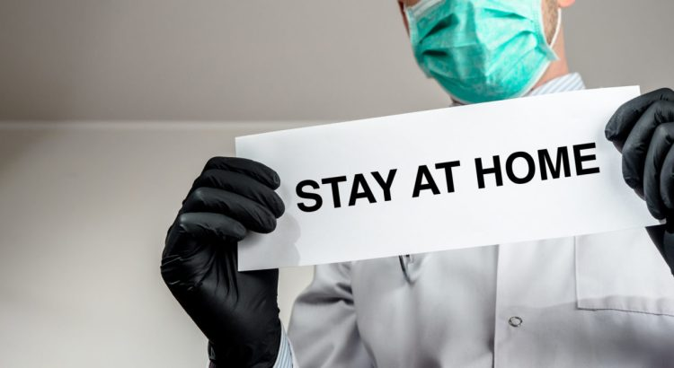 "A doctor holding a paper that reads ""stay at home"""