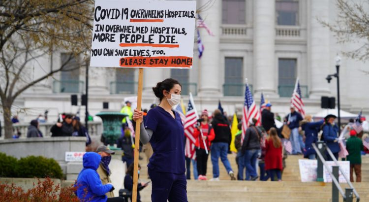 Madison, Wisconsin / USA - April 24th, 2020: Nurses at Reopen Wisconsin Protesting against the protesters protesting safer at home order rally holding signs telling people to go home.